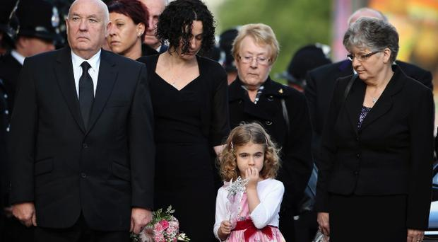 MANCHESTER, ENGLAND - OCTOBER 04: Greater Manchester Police constable Fiona Bone's mother June Bone (R), her father Paul Bone (L), her partner Clare Curran (centre left) and Miss Curran's five-year-old daughter Jessie watch as the coffin of Fiona Bone is taken into Manchester Cathedral for her funeral service on October 4, 2012 in Manchester, England. Police Constables Fiona Bone, 32, and her police colleague Nicola Hughes, 23, were killed as they responded to what they thought was a routine burglary call in Mottram, Greater Manchester and were murdered in a gun and grenade attack. The funeral of Nicola Hughes took place at the cathedral yesterday. Local man Dale Cregan, 29, appeared before Manchester Magistrates last week accused of four murders, including those of PC Nicola Hughes and PC Fiona Bone on September 18. (Photo by Dan Kitwood/Getty Images)