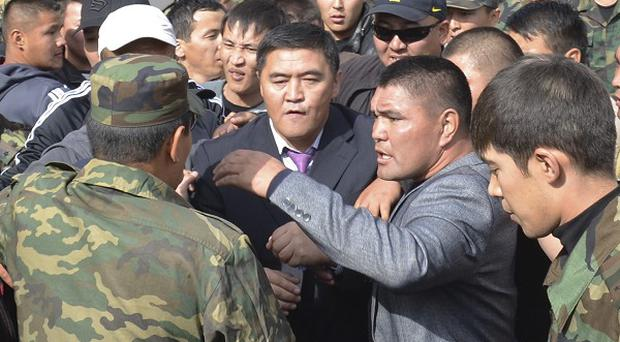 Guards protecting government headquarters, detain Kamchibek Tashiyev, who is surrounded by supporters (AP)