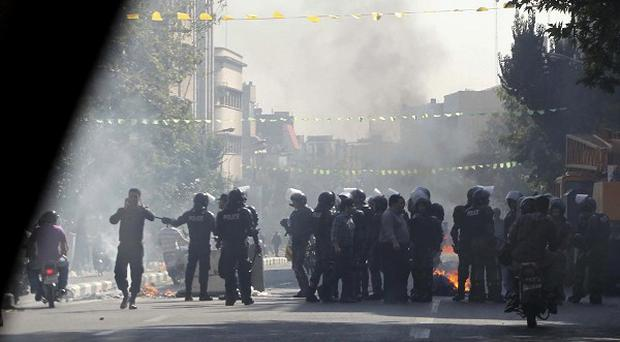 Iranian police officers block a street in Tehran amid protests over the country's currency crisis (AP)