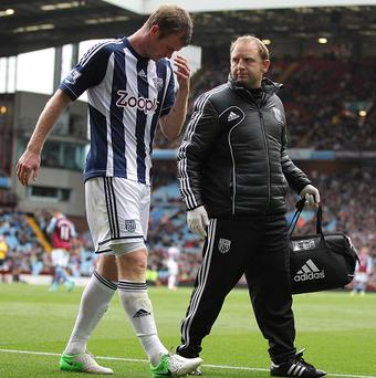 West Brom's Chris Brunt, left, leaves the pitch with an injury at Villa Park