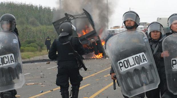 National civil police agents stand near a military truck in flames during clashes against the cost of electricity in Guatemala (AP)