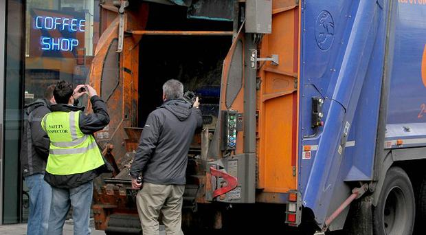 Health and Safety inspectors at the scene where a refuse collector was killed after becoming stuck in the back of a bin truck