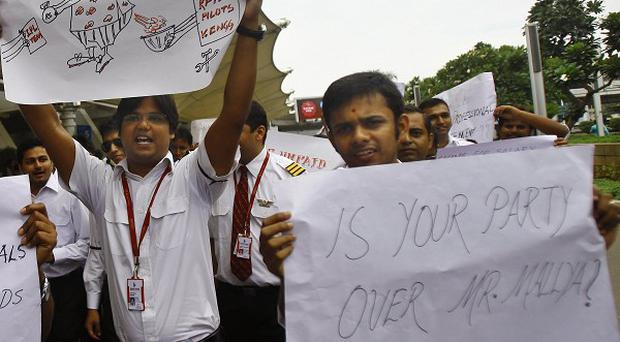 Kingfisher Airlines employees hold placards during a protest outside the domestic airport in Mumbai (AP)