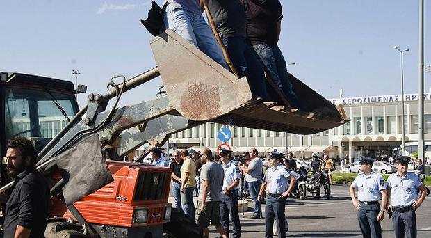 Farmers use tractors to block the entrance of the Iraklio International Airport, Crete, amid continued austerity protests (AP)