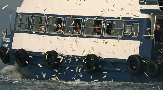 Relatives of victims who died in Monday's ferry collision in Hong Kong throw paper money to pay tribute to those lost (AP)