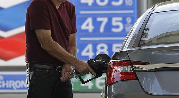 A man fills up at a fuel station in Sacramento as prices in California jumped to a new high (AP)