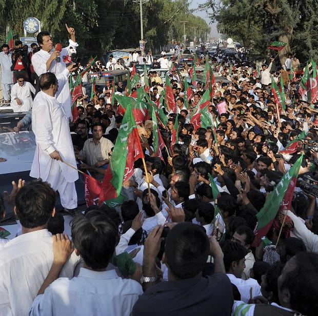Imran Khan, top left, addresses supporters during a peace march in Mianwali (AP)