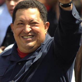 Venezuela's President Hugo Chavez waves as he arrives to a polling station in Caraca to cast his vote in the presidential election (AP)