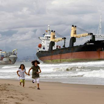 Two girls run in front of a cargo ship which ran aground after a heavy storm at Saler beach near Valencia (AP)