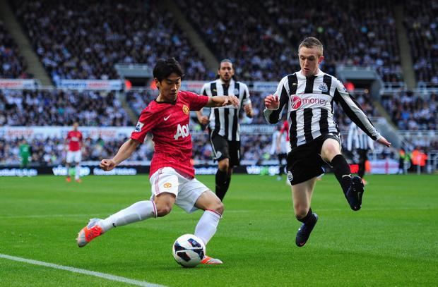 NEWCASTLE UPON TYNE, ENGLAND - OCTOBER 07: Man United player Shinji Kagawa (l) gets in a cross despite the challenge of Shane Ferguson during the Barclays Premier league game between Newcastle United and Manchester United at Sports Direct Arena on October 7, 2012 in Newcastle upon Tyne, England. (Photo by Stu Forster/Getty Images)