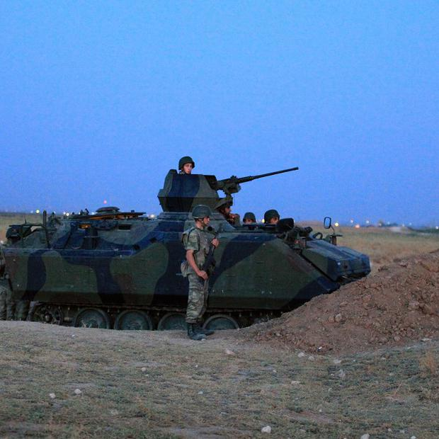 Turkish military stand near the Turkey-Syria border in Akcakale (AP)