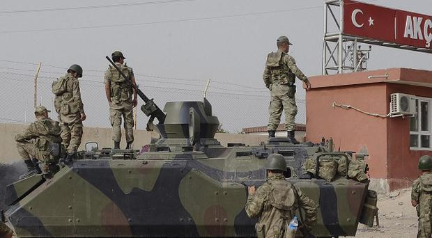 A Turkish military station at the border gate with Syria, across from the Syrian rebel-controlled Tel Abyad town, in Akcakale, Turkey (AP)