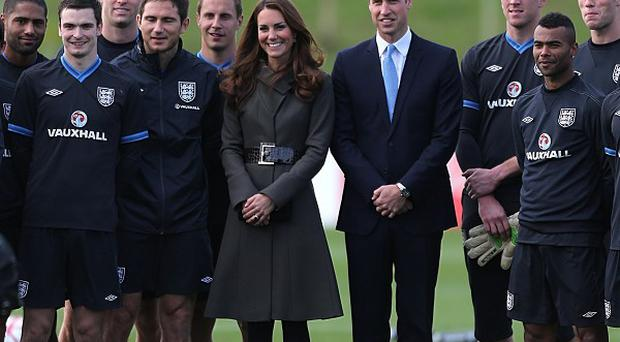 The Duke and Duchess of Cambridge pose for a photograph with the England squad