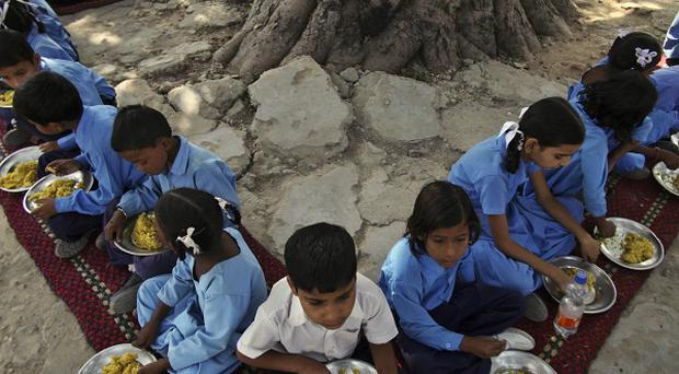 Schoolchildren eat a free midday meal, provided on all working days at a government school on the outskirts of Jammu, India (AP)