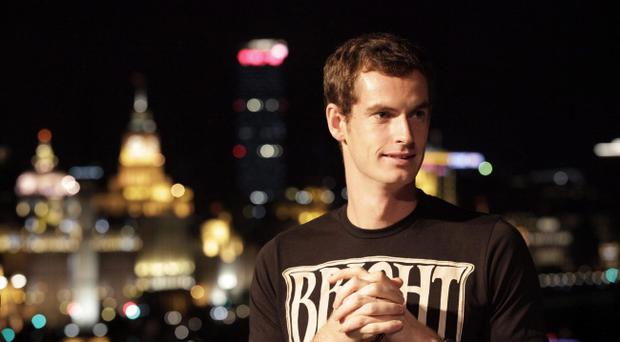 Andy Murray of Britain stands in front of the Bund, a famous waterfront as the symbol of town, during an event ahead of the Shanghai Masters tennis tournament in Shanghai, China, Sunday Oct. 7, 2012. (AP Photo/Eugene Hoshiko)