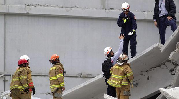 Firefighters look over the rubble after a section of a parking garage under construction at a college campus in Florida collapsed (AP)