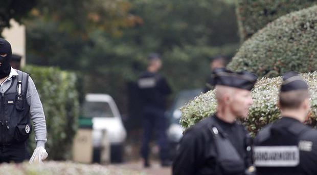 A hooded French police officer leaves a building where authorities discovered bomb-making material near Paris (AP)