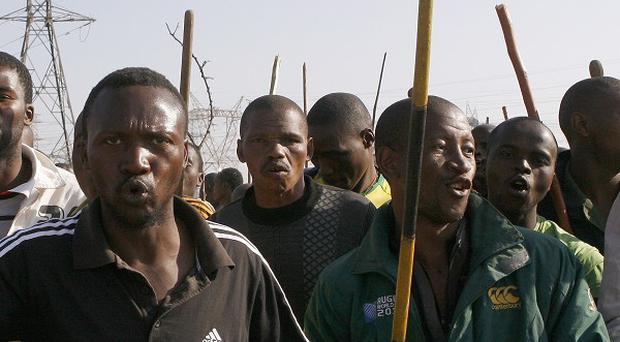 Mine workers sing at the Lonmin mine near Rustenburg during an earlier protest ((AP/Press Association images)