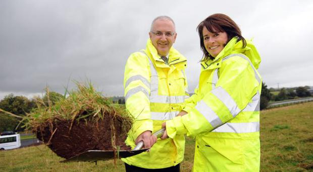 Regional Development Minister Danny Kennedy cuts the first sod on A8 project with Deirdre Mackle of Roads Service
