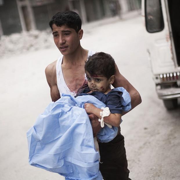 A Syrian youth holds a child wounded by Syrian Army shelling near Dar El Shifa hospital in Aleppo (AP)