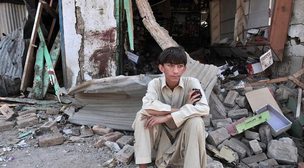A Pakistani youth sits amid the rubble of offices destroyed in a car bomb explosion in the Pakistani town of Darra Adam Khel (AP)