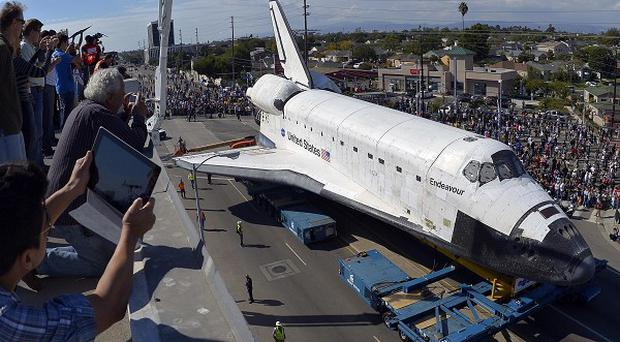Spectators take pictures from the roof of a building as the space shuttle Endeavour slowly moves along city streets in Los Angeles (AP)