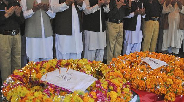 Pakistani police officers and officials pray next to the bodies of policemen who were killed by militants, during their funeral in Peshawar (AP Photo)