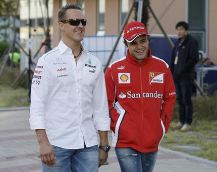 Mercedes driver Michael Schumacher of Germany (left) and Ferrari driver Felipe Massa of Brazil walk down the F1 paddock to the drivers meeting at the Korean Formula One Grand Prix at the Korean International Circuit in Yeongam, South Korea, Friday, Oct. 12, 2012. (AP Photo/Lee Jin-man)