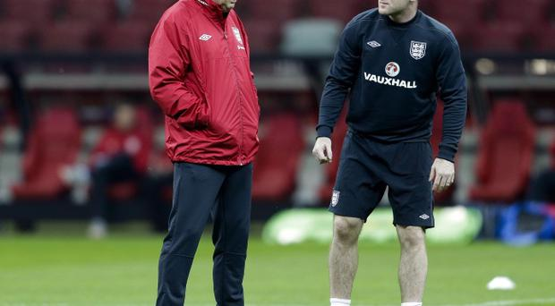England's soccer manager Roy Hodgson (left) talks to player Wayne Rooney, during a training session, at the National Stadium in Warsaw, Monday, Oct. 15, 2012. England will play Poland in a World Cup Group H qualifying soccer match on Tuesday. (AP Photo/Markus Schreiber)