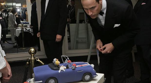 Prince William looks at a special cake re-enacting the scene from his wedding at a dinner in aid of the St Giles Trust (AP Photo)