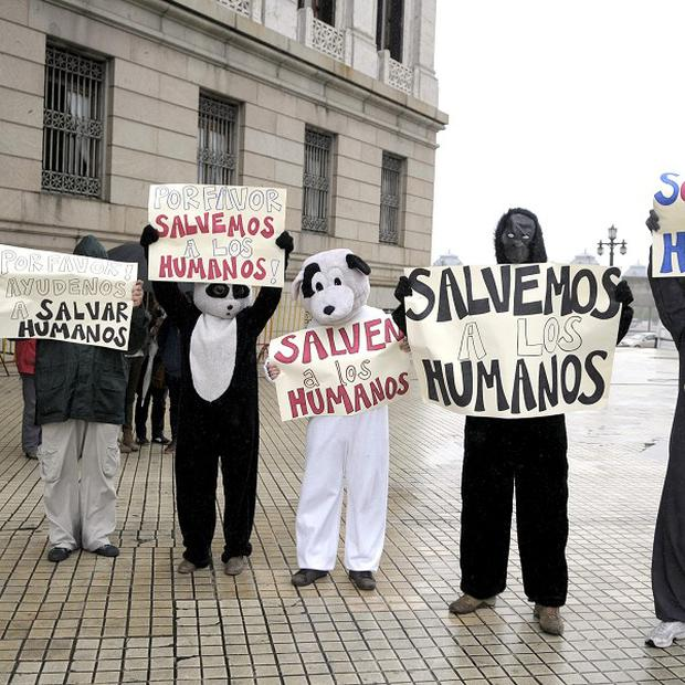 Pro-life demonstrators dressed in animal costumes holding protest signs that read 'save the humans' in Uruguay (AP)