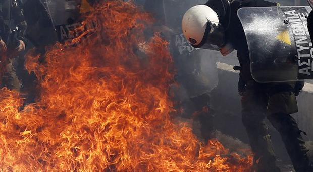 Protesters throw petrol bombs at riot police officers during a 24-hour nationwide general strike in Athens (AP)