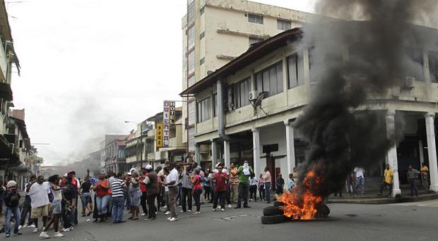 Protesters block a road with burning tires as they protest in Colon, Panama (AP)