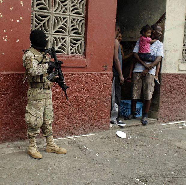 A masked police officer stands guard as residents look out from the doorway of their home in downtown Colon, Panama (AP/Arnulfo Franco)