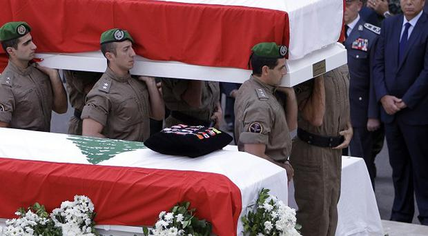 Members of Lebanese police intelligence division units carry the coffins of Brig Gen Wissam al-Hassan and his bodyguard (AP)