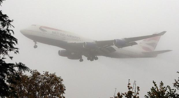 A plane lands in the mist at Heathrow Airport as early-morning fog disrupted flights at airports