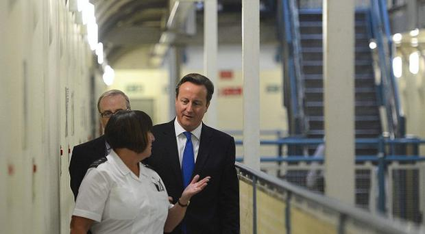 David Cameron, right, is escorted around C wing by prison officer Margaret Vaughan, during his visit to Wormwood Scrubs in west London