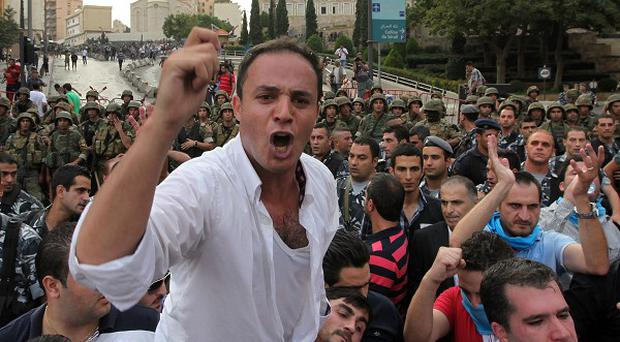 Protesters chant slogans against the Lebanese government after the funeral of Brig Gen Wissam al-Hassan in Beirut (AP)