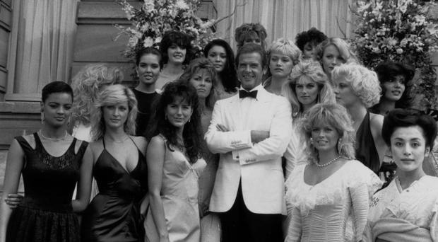 Bond Beauties... 17th August 1984: Film star Roger Moore (James Bond) and the Bond Girls from the film 'View to a Kill' directed by John Glen. (Photo by Larry Ellis/Express/Getty Images)Back row - right in front of flowers on the left - is Celine Cawley.