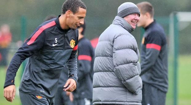 Manchester United's Rio Ferdinand with manager Sir Alex Ferguson during a training session yesterday at Carrington Training Ground, Manchester