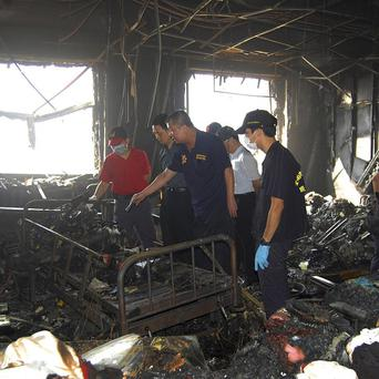 Investigation teams search for possible causes of a fire that swept through a nursing home in Taiwan (AP)