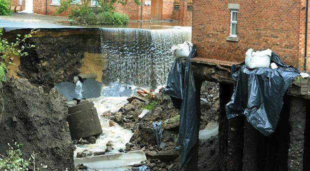 Water cascades past a block of townhouses in Newburn, Newcastle after floods left them in a state of collapse
