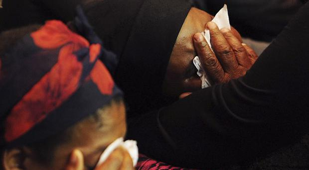 A woman sobs as video of South African miners being shot by police is shown at an inquiry (AP)
