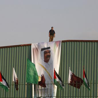 A Palestinian worker stands above a poster of the Emir of Qatar Sheikh Hamad bin Khalifa al-Thani (AP)