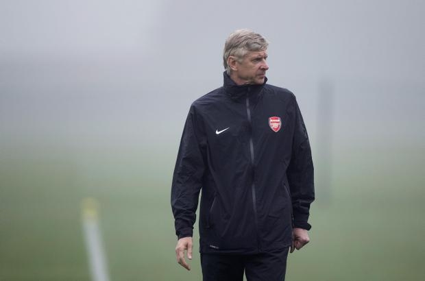 Arsenal's French manager Arsene Wenger stands in the mist during a training session at the club's facilities in London Colney, England, Tuesday, Oct. 23, 2012. Arsenal are due to play FC Schalke 04 in a Group B Champions League soccer match at the Emirates Stadium in London on Wednesday. (AP Photo/Matt Dunham)