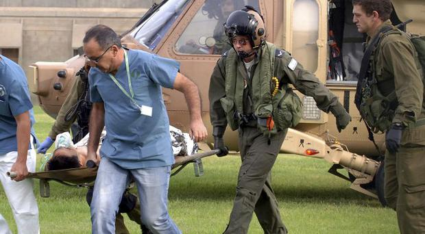 A man wounded by a mortar shell fired from the Gaza Strip is stretchered into hospital in Beersheba, southern Israel (AP)