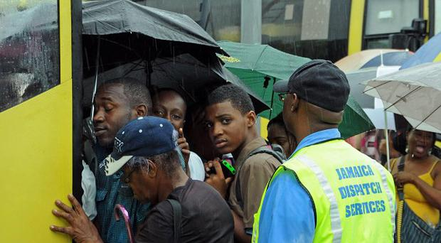Commuters board a bus as rain brought by the outer bands of Tropical Storm Sandy falls in Kingston, Jamaica (AP/Collin Reid)
