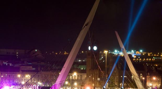 Derry shines in the light last night to mark the 2013 City of Culture as the Peace Bridge is illuminated with spot lights and blue search lights rise over Derry to mark the launch of the 2013 programme of events. Picture Martin McKeown. Inpresspics.com. 25.10.12