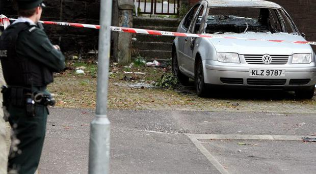 Police stand by a burnt out car in west Belfast, which is linked to a fatal shooting in Newtownabbey, Co Antrim, last night. PRESS ASSOCIATION Photo.