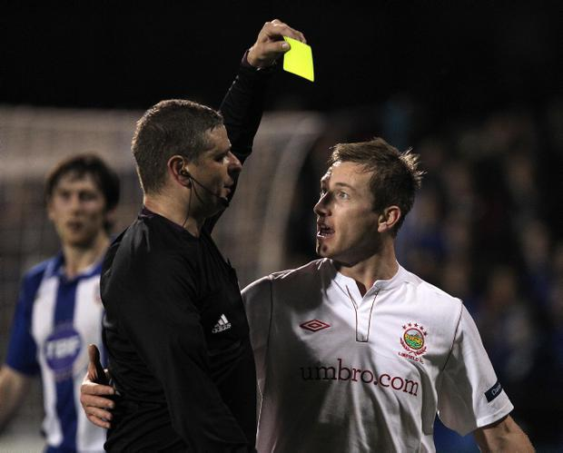 Referee Raymond Crangle shows Mark McAllister a yellow card in Monday night's game